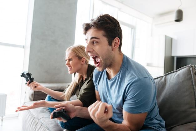 Junger mann, der siegergeste beim spielen mit seiner frau in den videospielen zeigt
