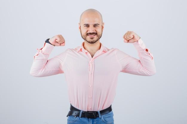 Junger mann, der siegergeste im hemd, in den jeans zeigt und glücklich schaut. vorderansicht.
