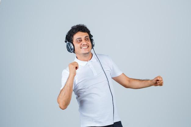 Junger mann, der siegergeste im weißen t-shirt zeigt und glückselig aussieht. vorderansicht.