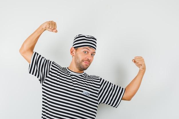 Junger mann, der siegergeste in gestreiftem t-shirt, hut und fröhlich aussehend zeigt.