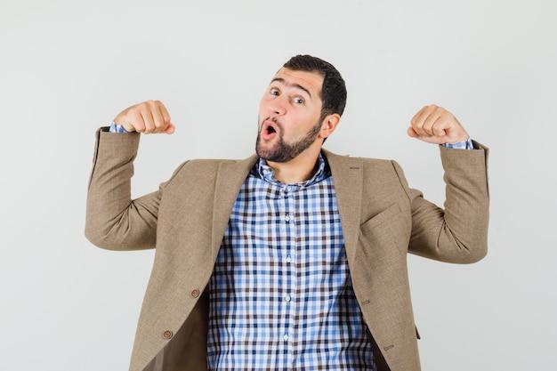 Junger mann, der siegergeste in hemd, jacke zeigt und glückselig aussieht