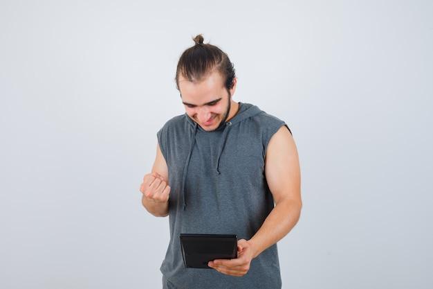 Junger mann, der siegergeste zeigt, rechner im kapuzenpulli hält und fröhlich, vorderansicht schaut.