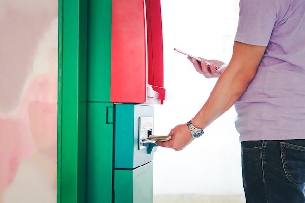 Junger mann, der smartphone hält und atm-geldautomaten verwendet
