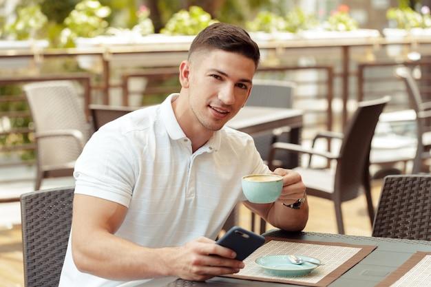 Junger mann, der smartphone im café verwendet