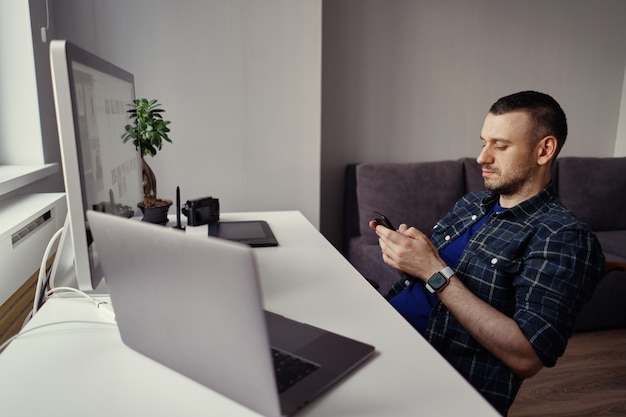 Junger mann, der smartphone in händen hält, während eine pause im heimbüro macht