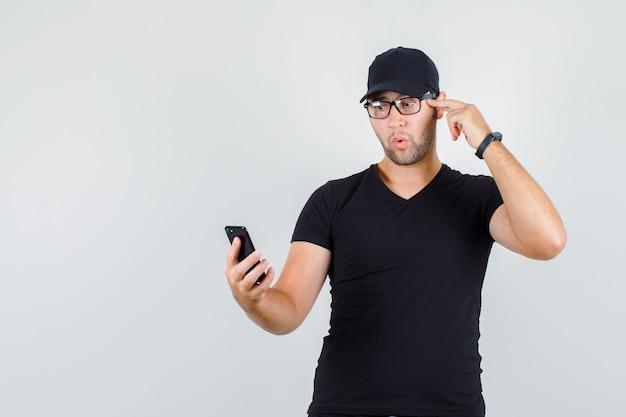 Junger mann, der smartphone mit finger auf schläfen im schwarzen t-shirt betrachtet