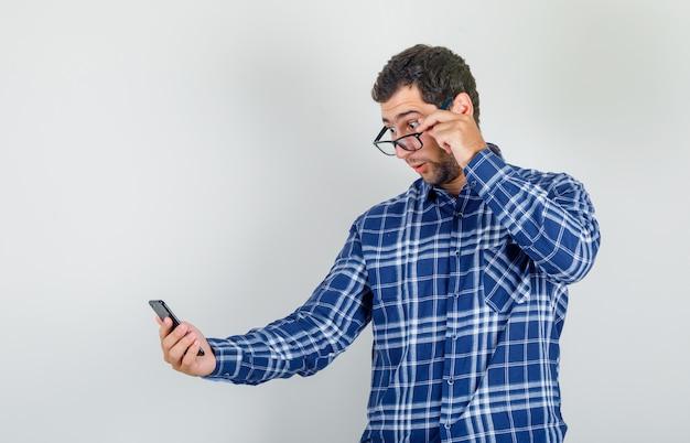 Junger mann, der smartphone über brille im karierten hemd betrachtet und schockiert schaut