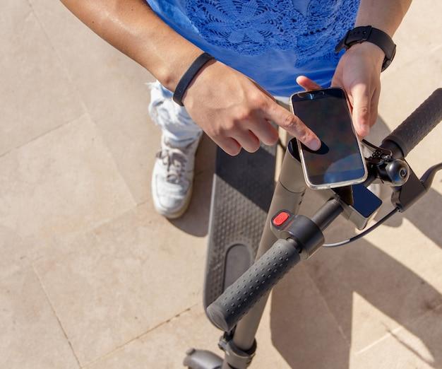 Junger mann, der smartphone verwendet, um einen geteilten elektroroller nahaufnahme zu entsperren