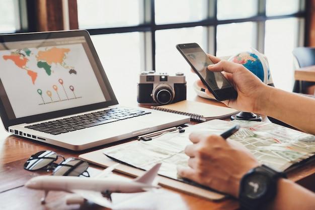 Junger mann, der smartphoneplanungs-urlaubsreise verwendet
