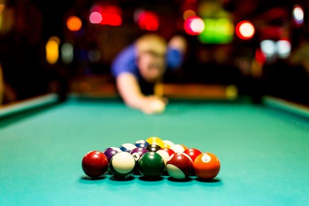 Junger mann, der snooker in der bar spielt