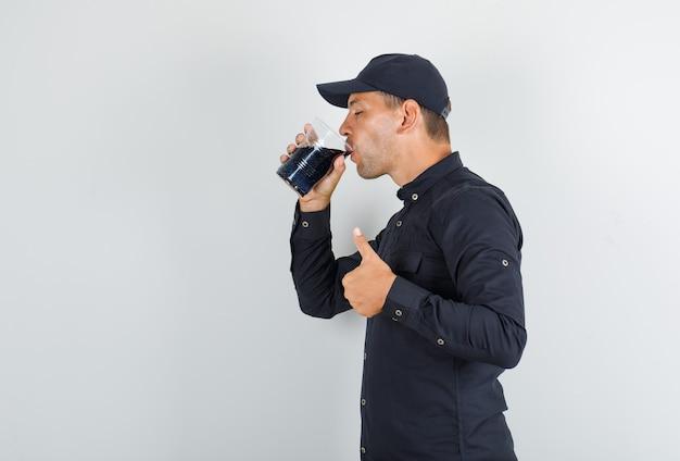 Junger mann, der soda mit daumen oben im schwarzen hemd trinkt