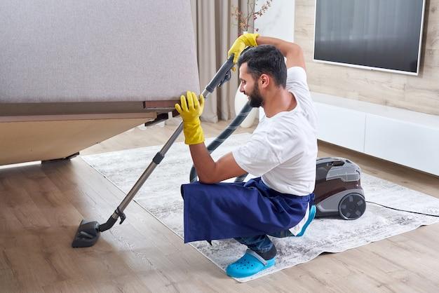 Junger mann, der sofa mit staubsauger beim verlassen des raumes zu hause reinigt