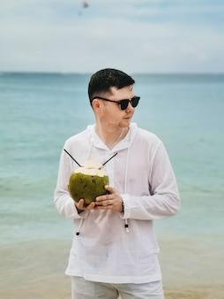 Junger mann der sommerferien in der sonnenbrille, die auf dem blauen meer abkühlt und kokosnuss trinkt