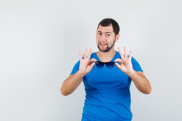 Junger mann, der sonnenbrille im blauen t-shirt hält und zuversichtlich schaut