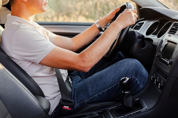Junger mann, der sorgfältig das auto fährt