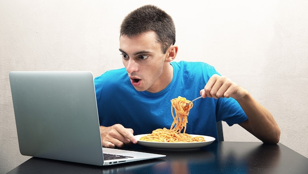 Junger mann, der spaghetti mit tomatensauce isst und den computer beobachtet