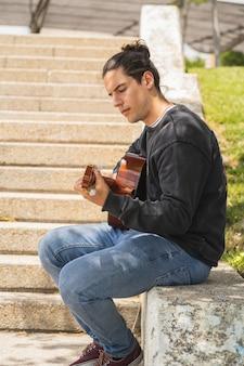 Junger mann, der spanische gitarre auf dem feld spielt