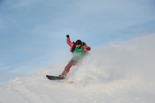 Junger mann, der spaß hat, auf den snowboard zu schieben