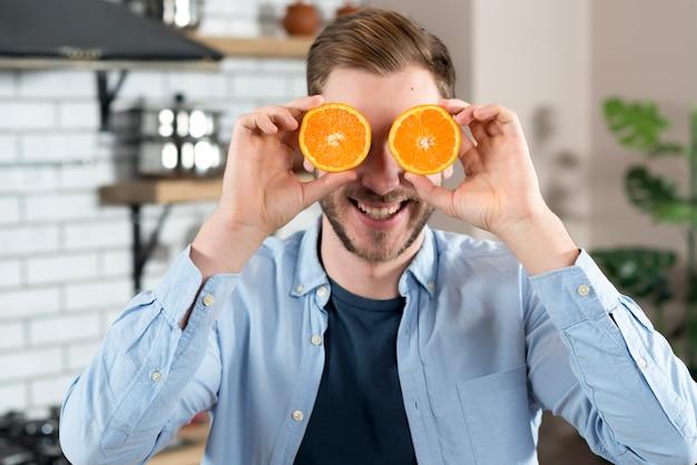 Junger mann, der spaß mit zwei orangenscheibe zu hause macht
