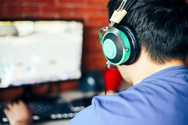 Junger mann, der spiel am computer spielt