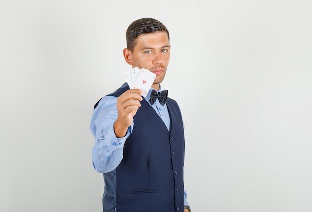Junger mann, der spielkarten im anzug hält