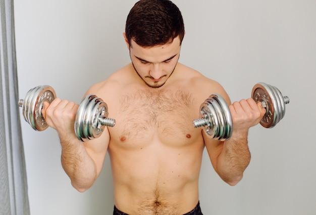 Junger mann, der sportübungen zu hause macht