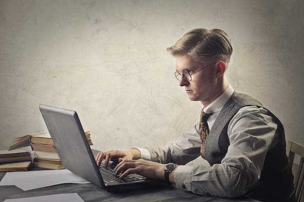 Junger mann, der stark auf einem laptop studiert