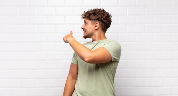 Junger mann, der steht und auf objekt auf kopienraum zeigt, rückansicht