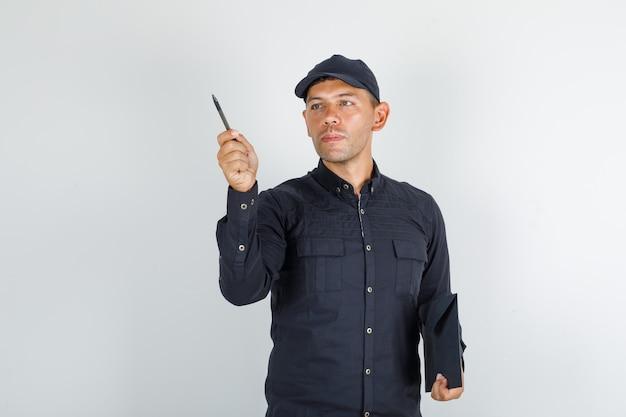 Junger mann, der stift und ordner im schwarzen hemd mit kappe hält