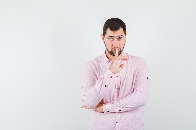 Junger mann, der stille geste im rosa hemd zeigt und vorsichtig schaut