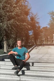 Junger mann, der stillsteht, nachdem sport im park getan worden ist