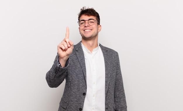 Junger mann, der stolz und zuversichtlich lächelt und die nummer eins triumphierend posiert und sich wie ein anführer fühlt