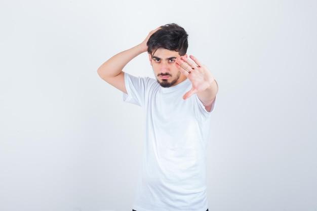 Junger mann, der stop-geste im t-shirt zeigt und selbstbewusst aussieht looking