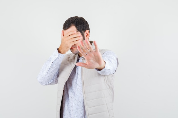Junger mann, der stoppgeste im hemd zeigt Kostenlose Fotos