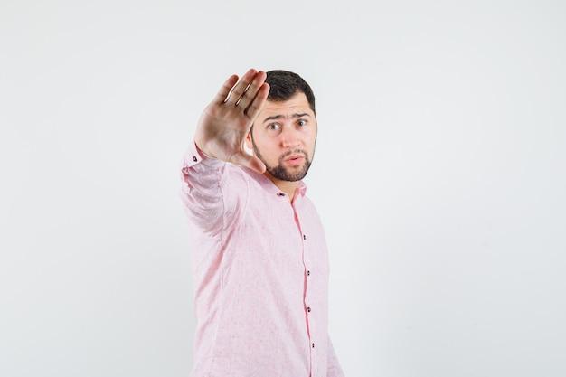 Junger mann, der stoppgeste im rosa hemd zeigt und ernst schaut