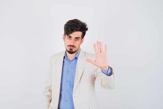 Junger mann, der stoppschild in blauem t-shirt und weißer anzugjacke zeigt und ernst aussieht