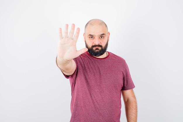 Junger mann, der stoppschild in rosa t-shirt zeigt und ernst, vorderansicht schaut.
