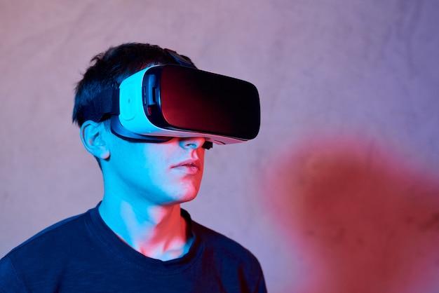 Junger mann, der sturzhelm der virtuellen realität verwendet