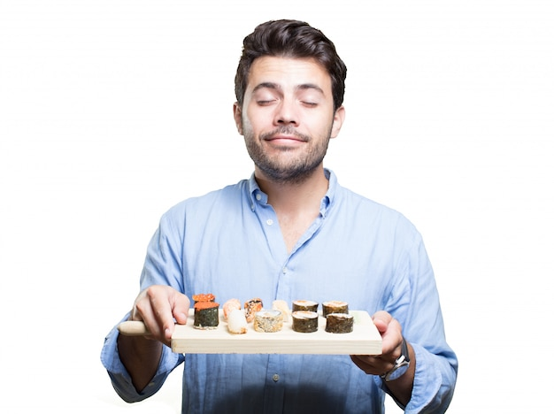 Junger mann, der sushi auf weißem hintergrund isst