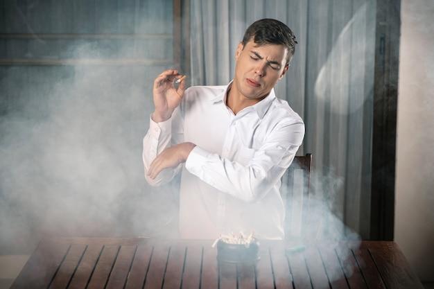 Junger mann, der tabakrauch abwehrt, an einem tisch sitzt, auf dem ein voller aschenbecher steht, und eine brennende zigarre in der hand hält. der geruch von zigaretten.