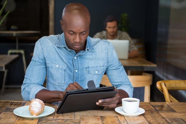 Junger mann, der tablet-computer am tisch im kaffeehaus verwendet