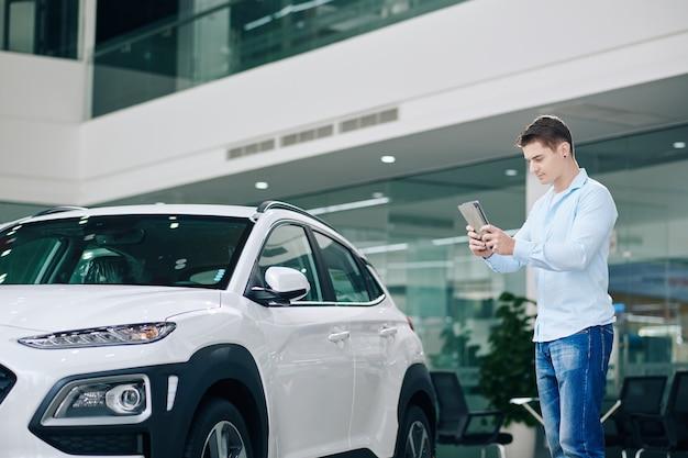 Junger mann, der tablet-computer verwendet, um fotos von auto zu machen, das er im autohaus mag
