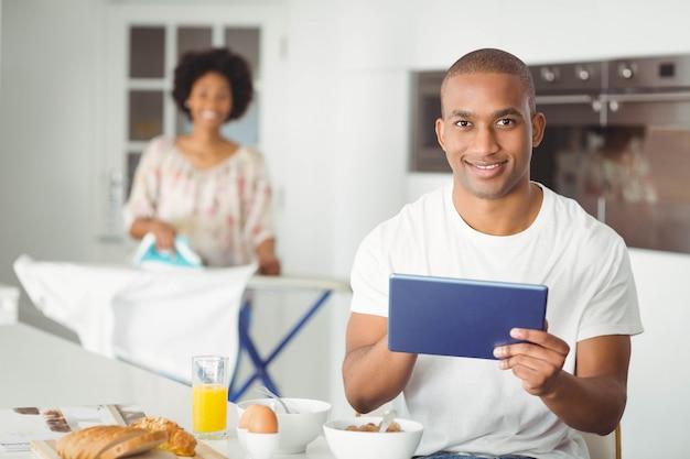 Junger mann, der tablette im küchen- und freundinbügeln verwendet