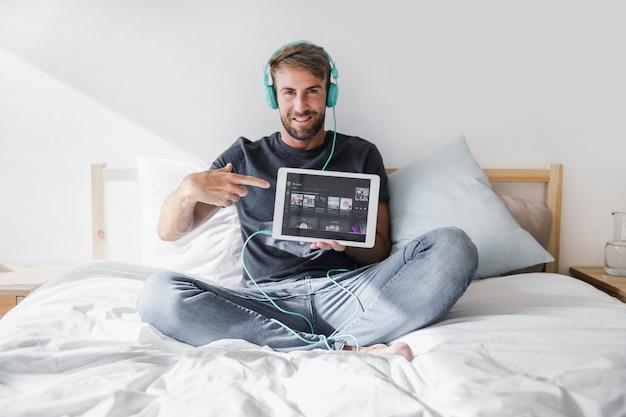 Junger mann, der tablette mit spotify app hält