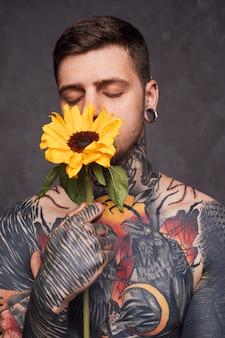 Junger mann der tätowierung mit dem halten der sonnenblume vor seinem mund gegen grauen hintergrund