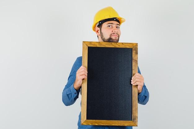 Junger mann, der tafel im hemd, im helm hält und optimistisch, vorderansicht schaut.