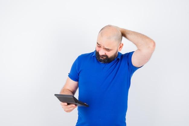 Junger mann, der taschenrechner betrachtet, während er die hand auf dem kopf im blauen hemd hält und verloren aussieht. vorderansicht.
