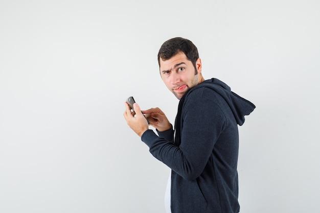 Junger mann, der taschenrechner hält und einige operationen auf ihm im weißen t-shirt und im schwarzen kapuzenpullover mit reißverschluss vorne ausführt und ernsthafte vorderansicht sieht.