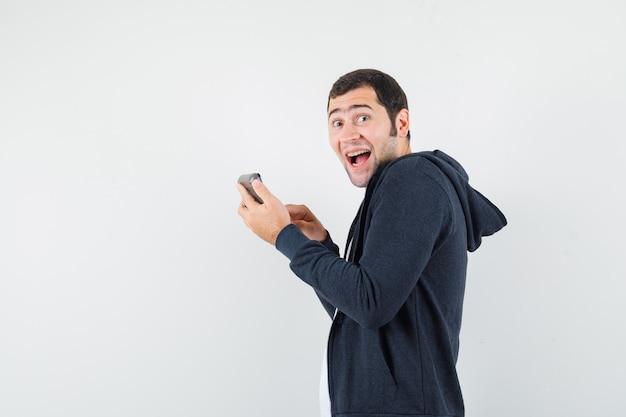 Junger mann, der taschenrechner hält und einige operationen daran in weißem t-shirt und schwarzem kapuzenpullover mit reißverschluss vorne durchführt und überrascht aussieht, vorderansicht.