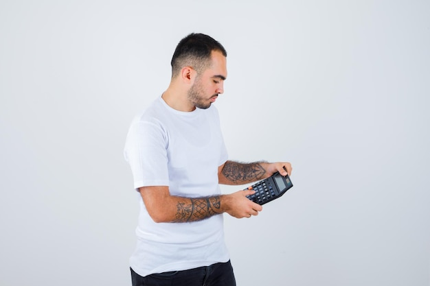 Junger mann, der taschenrechner hält und operationen in weißem t-shirt und schwarzer hose durchführt und ernst aussieht